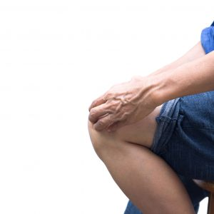 Senior woman sit on the chair with knee and joint pain isolated